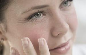 Mulher tocando o rosto com a mão